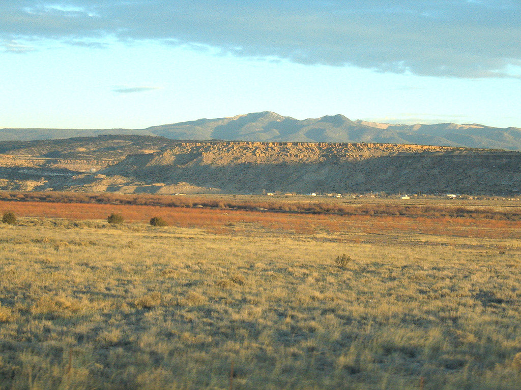 Around Casablanca, NM, west of Albuquerque, NM<br /> <br /> At 6:50a the sun is up in all its glory, painting a golden hue to the red grasses of the high desert and magnifying the deep red color of the surrounding mesas.  Around Grants, NM we see miles and miles and miles of lava.  I don't normally think of this area as having volcanic eruptions.