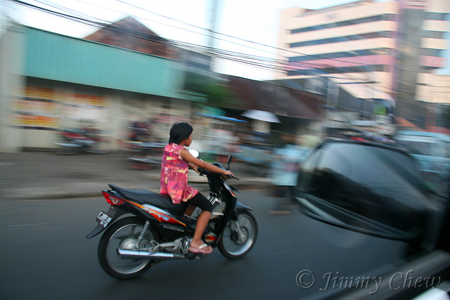 """<font color=""""yellow"""">A pan shot of a girl too young for her age to ride a bike.</font><br>"""