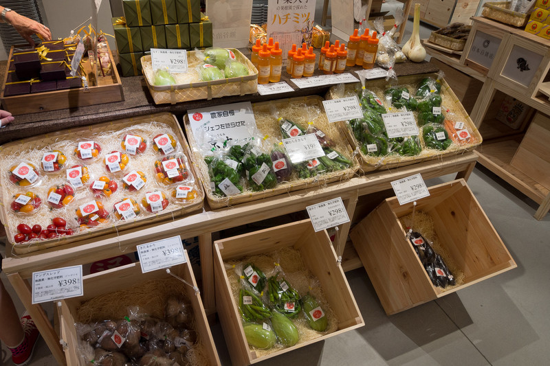Inside a high end specialty food store.  Indivually wrapped produce items.