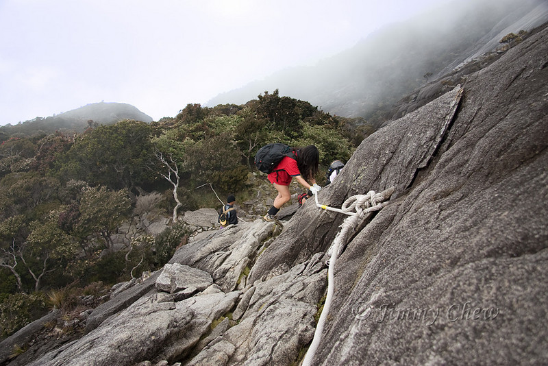 Joanne traversing the steep rock with the aid of the rope.