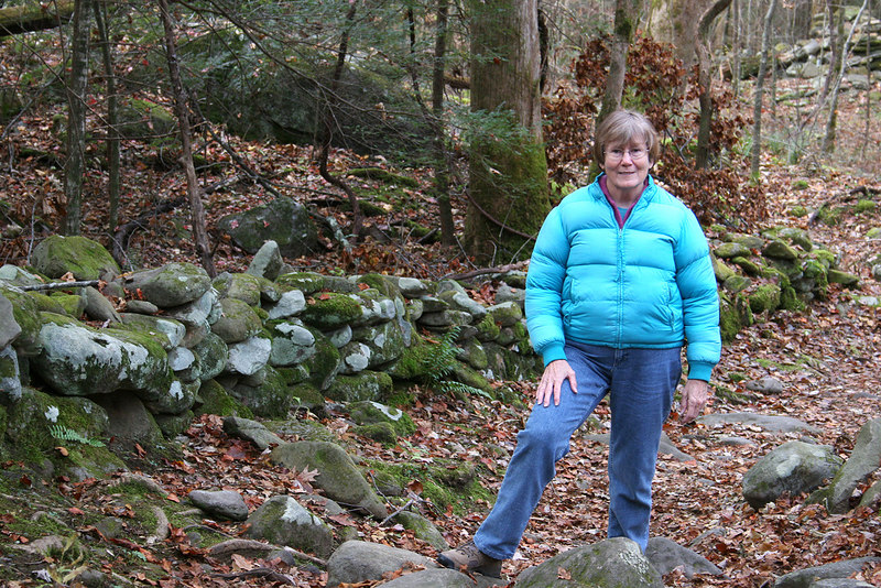 Susan along nature trail at Ogle farm with stone walls in background