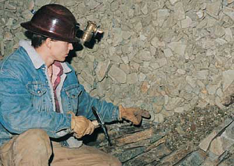 He is pointing out where the rock and gravel ends and the bedrock begins.  Miners cut tunnels to dig down to bedrock.