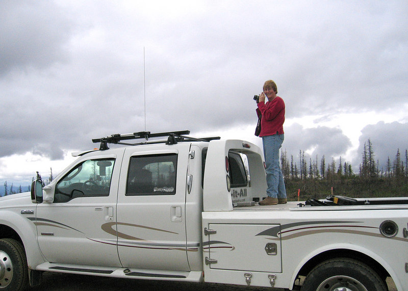 Susan standing on truck to take picture