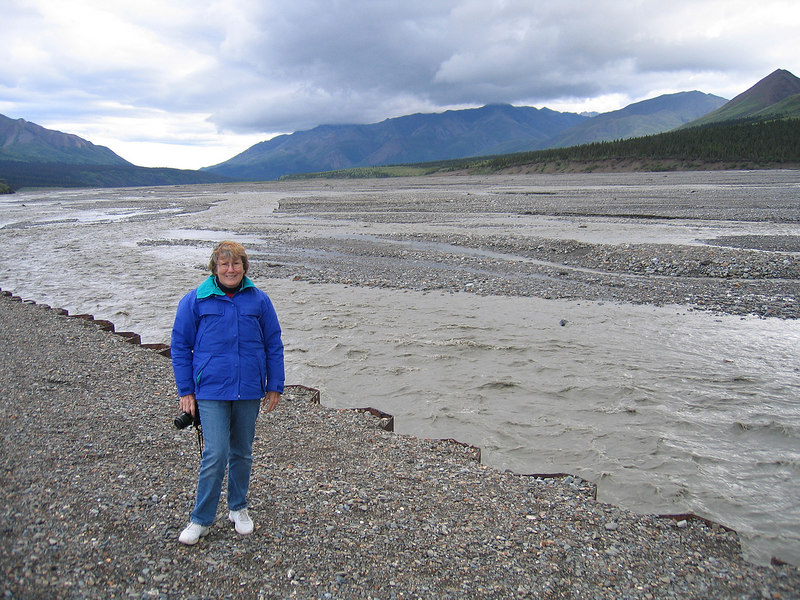 Susan at Toklat River Rest Stop with Toklat River in background