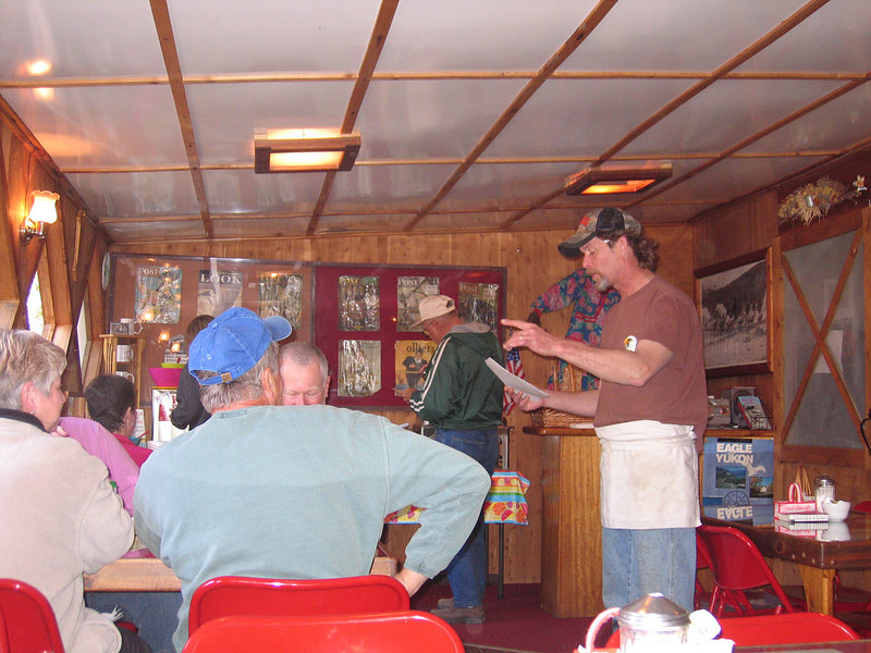 The owner of Sourdough Campground giving some of the pancake toss winners a certificate the next morning at breakfast