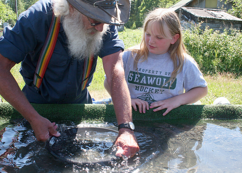 Gold Rush Peck showing girl how to pan for gold in Hope, AK