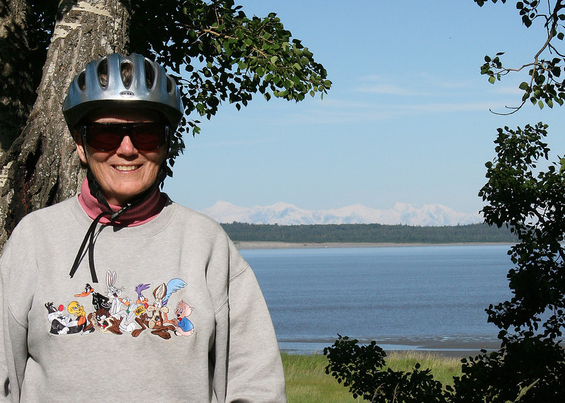 Susan on bike trail with the snow capped mountains behind