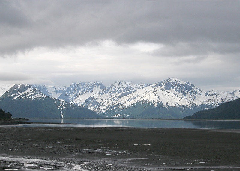 Mud flats in Turnagain Arm with the snow clad mountains reflecting in the inlet
