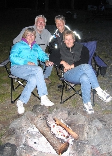Mike and Susan enjoying campfire and Swiss coffee with two new Swiss friends; Nora in front and Regula next to Mike