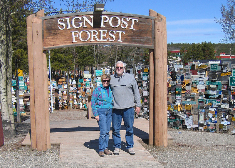 Susan and Mike in front of the Sign Post Forest in Watson Lake, YT