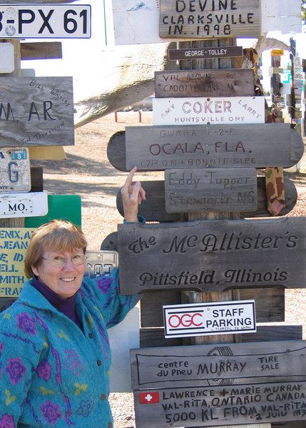 Susan pointing to a sign from Ocala, FL at the Sign Post Forest in Watson Lake, YT