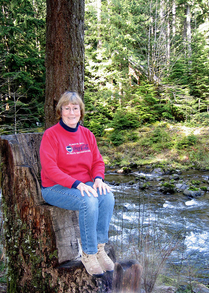 Susan sitting in carved out seat by Sandy River in Tollgate Park, OR