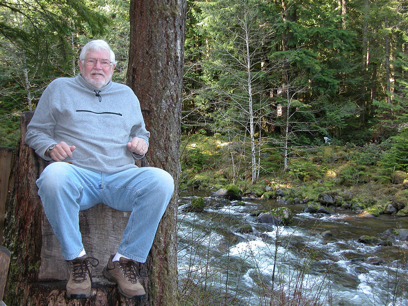 Mike sitting in carved out seat by the Sandy River in Tollgate Park, OR