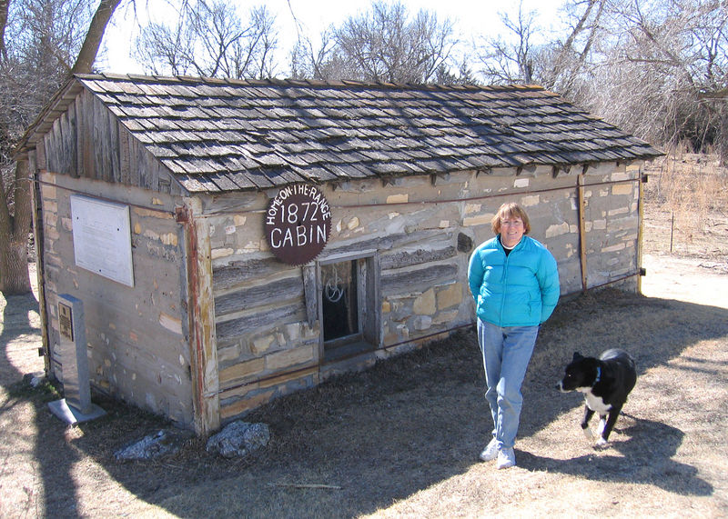 Susan beside the cabin.  The outside was made of wood and covered in spots by what looked like clay.