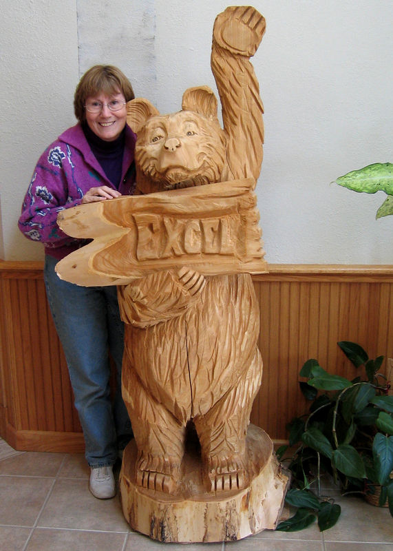 Susan in lobby of plant with the Excel bear