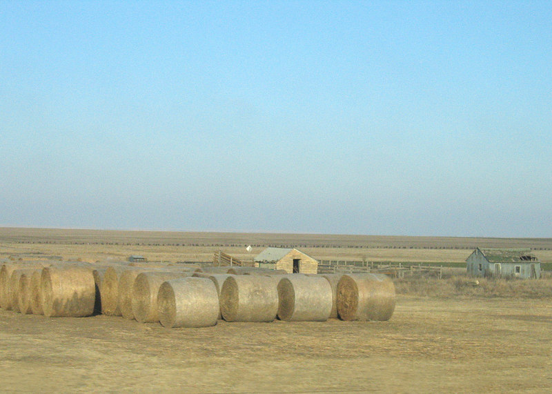 Rolls of hay and barn along route 283 in Kansas