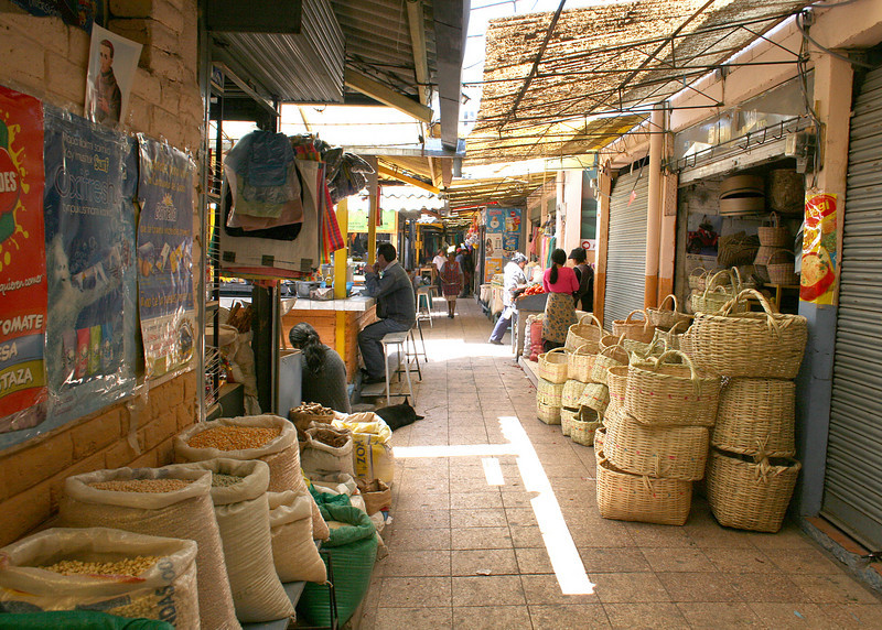 Looking down one of the aisles in the market place.  Bags of grains and stacks of baskets.