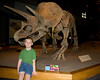 John sitting with his favorite dinosour, the Triceratops.