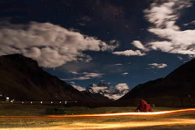 Mt. Everest by Moonlight.  A passing service vehicle made the streaks of light.  At the left edge is the Rongphu Monastery.