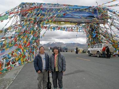 Qomolungma National Nature Preserve Entrance.  Prayer flags virtually enshroud the entrance gate, as they do at every other roadside stopping point with something tall nearby, whether man-made or natural.