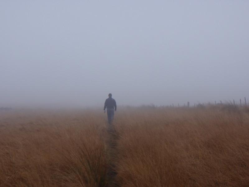 Nigel hiking on the foggy mooors.