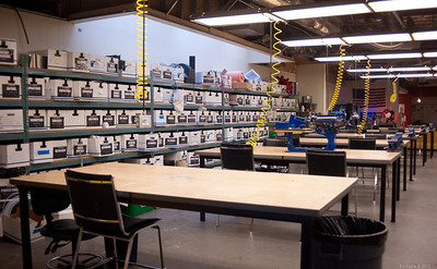 Workbenches with lots of room to spread out, each with AC lines and compressed air fed from overhead.   [TechShop Menlo Park]