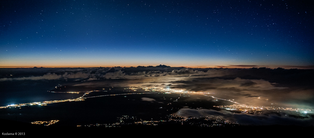 The lights of central Maui.  Kahului-Wailuku to the right, and Kihei-Maalaea to the left.  The West Maui Mountains are shrouded in clouds.