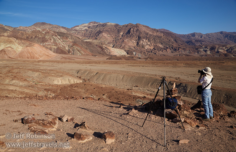 Lynda taking photos beside my tripod and camera bag of multiple colors of reds, browns, and faint greens in the mountains under deep blue sky. (3/17/2013, Artists Drive Loop, Death Valley NP)<br /> <br /> EF24-105mm f/4L IS USM @ 24mm f/11 1/160s ISO125