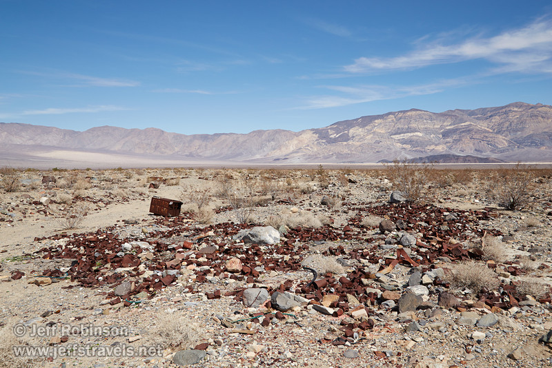 """NE view of rusted junk behind the RV park, including a metal bin labeled """"Futurism = Turism"""". The Panamint Valley, Panamint Dunes (sandy area on left in front of the mountains) and the Panamint Range are in the background. (3/17/2013, Panamint Springs Resort, Death Valley Trip)<br /> <br /> EF24-105mm f/4L IS USM @ 28mm f/9 1/320s ISO125"""