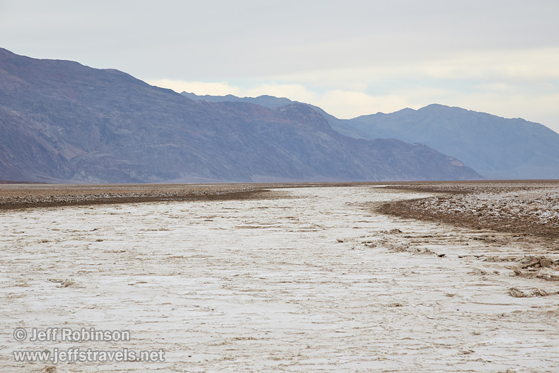 Southerly view of a white stripe of the crystallized salt basin bending through the brownish, rougher salt on the edges, with mountains in the distance under cloudy skies. (3/19/2013, West Side Road, Death Valley NP)<br /> EF24-105mm f/4L IS USM @ 105mm f/8 1/200s ISO400