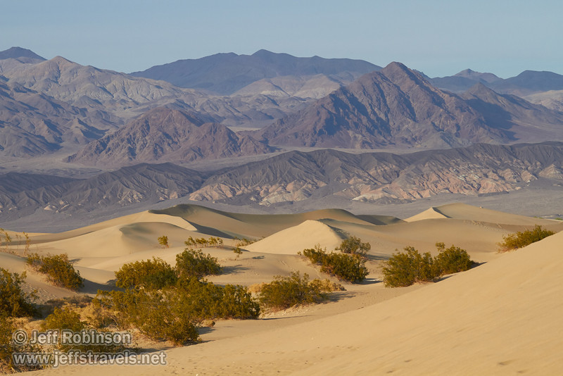 Footprints and creosote bushes dominate the nearer sand dunes, with larger dunes beyond. Mountains of the Amargosa Range are in the background.(3/19/2013, Mesquite Flat Sand Dunes, Death Valley NP)<br /> EF100-400mm f/4.5-5.6L IS USM @ 105mm f/8 1/800s ISO400