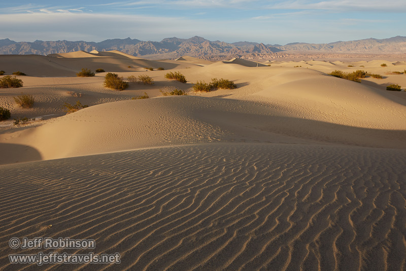 Late sun highlights the ripples in the textured sand of a dune in the foreground, with a photographer and the larger of the Mesquite Flat Sand Dunes beyond. The Grapevine Mountains of the Amargosa Range are in the background. (3/19/2013, Mesquite Flat Sand Dunes, Death Valley NP)<br /> TS-E24mm f/3.5L II @ 24mm f/8 1/400s ISO400