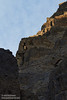 Sun clips the top of the blocky-cliff wall, with the rest of the wall in shade under mostly-cloudy skies. There is a small window visible in the wall. (3/20/2013, Titus Canyon, Death Valley NP)<br /> EF100-400mm f/4.5-5.6L IS USM @ 200mm f/7 1/400s ISO400