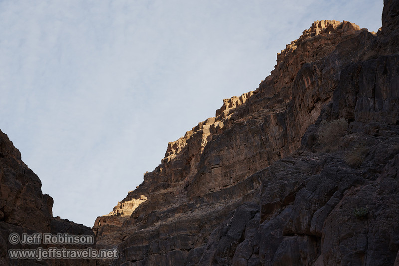 Sun clips the top of the blocky-cliff wall, with the rest of the wall in shade under mostly-cloudy skies. There is a small window visible in the wall. (3/20/2013, Titus Canyon, Death Valley NP)<br /> EF24-105mm f/4L IS USM @ 60mm f/8 1/200s ISO200