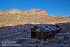 A couple of rusted corrugated metal buildings from the ghost town of Leadfield in deep shade in the foreground, with the colorful desert mountains in full sun under blue sky in the distance. (3/21/2013, Leadfield (ghost town), Titus Canyon Road, Death Valley NP)<br /> EF24-105mm f/4L IS USM @ 24mm f/13 1/100s ISO200