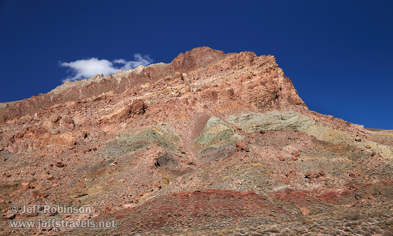 A mountain with hues of greens, yellows, reds, and browns under deep blue sky with one cloud over it. (3/21/2013, Titus Canyon Road, Death Valley NP)<br /> EF24-105mm f/4L IS USM @ 40mm f/7 1/200s ISO200