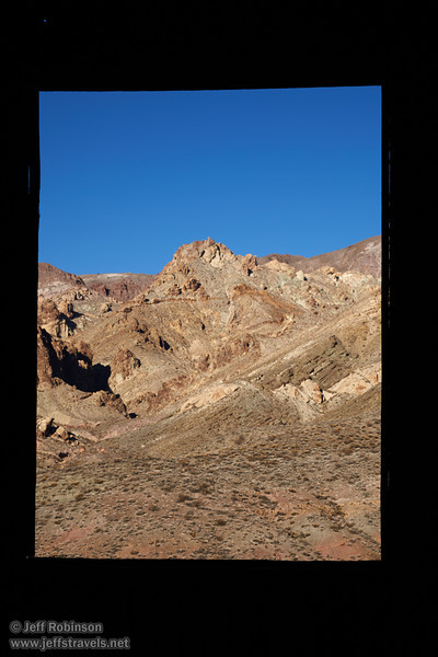 The window of an old building frames a foreground in deep shade, with a sunlit mountainside beyond with hues of greens, yellows, reds, and browns under blue sky. (3/21/2013, Leadfield (ghost town), Titus Canyon Road, Death Valley NP)<br /> EF24-105mm f/4L IS USM @ 60mm f/11 1/100s ISO100