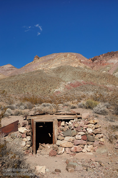 A small storage building built of wood, corrugated metal, and rock is built into the hill side in the ghost town of Leadville. In the background is a mountain with hues of reds, browns, yellows, greens under blue sky with one wispy cloud. (3/21/2013, Leadfield (ghost town), Titus Canyon Road, Death Valley NP)<br /> EF24-105mm f/4L IS USM @ 47mm f/11 1/200s ISO400