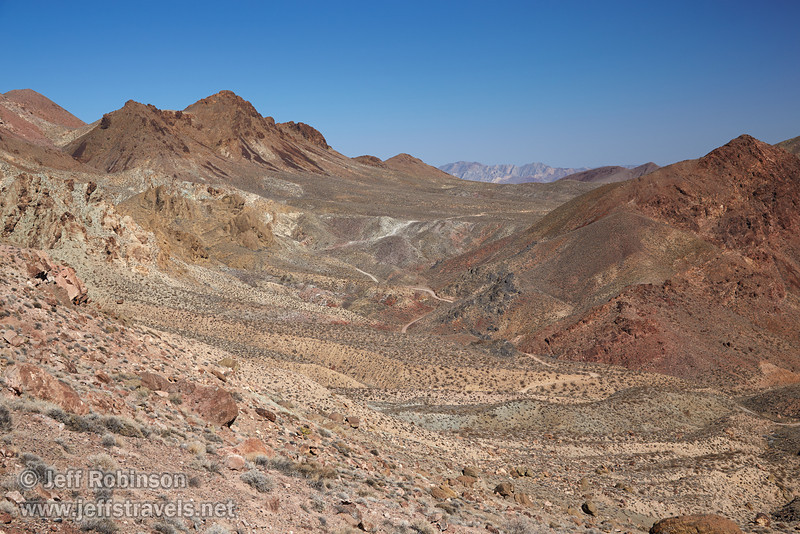 Easterly view of Titus Canyon Road twisting through a valley. The hillsides and mountains have shades of reds, yellows, greens, and browns under blue sky. (3/21/2013, Red Pass, Titus Canyon Road, Death Valley NP)<br /> EF24-105mm f/4L IS USM @ 50mm f/8 1/250s ISO200