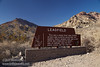 A brown, wooden NPS sign with a brief description of Leadfield, with colorful desert mountains behind. (3/21/2013, Leadfield (ghost town), Titus Canyon Road, Death Valley NP)<br /> EF24-105mm f/4L IS USM @ 28mm f/8 1/125s ISO400