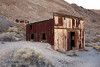 A rusted yellowish building made of corrugated metal in the foreground leads to another in the background, with both buildings still largely intact. (3/21/2013, Leadfield (ghost town), Titus Canyon Road, Death Valley NP)<br /> EF24-105mm f/4L IS USM @ 32mm f/8 1/125s ISO400
