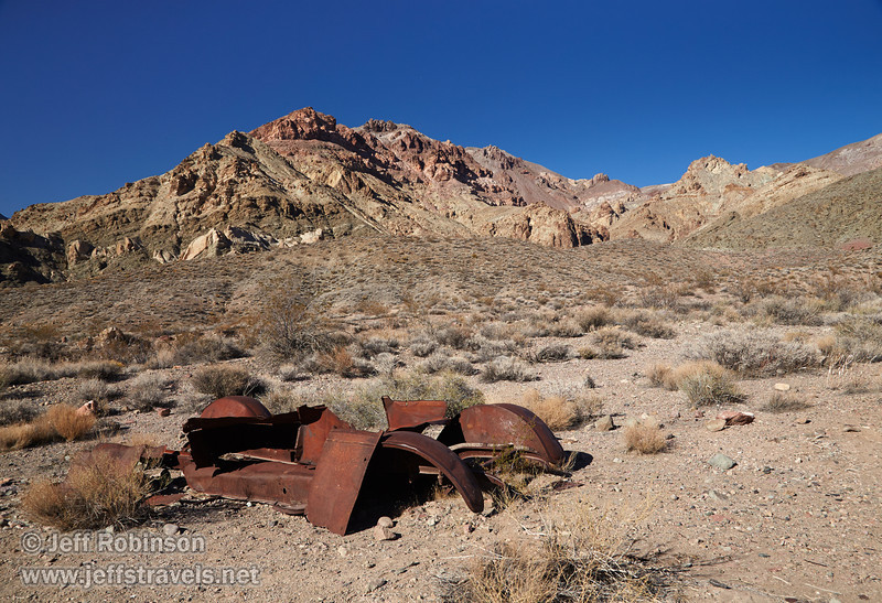 The remains of an old rusted car in the foreground offset the mountain beyond with hues of greens, yellows, reds, and browns under deep blue sky. (3/21/2013, Leadfield (ghost town), Titus Canyon Road, Death Valley NP)<br /> EF24-105mm f/4L IS USM @ 28mm f/11 1/200s ISO400