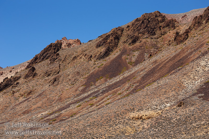 Pale green brush on the foreground slopes lead to sharper mountains under blue sky. Rock colors include yellows and reds. You can see how the red rock has broken off the mountain to form rock slides, and darker-green bushes grow around those slides. (3/21/2013, Titus Canyon Road, Death Valley NP)<br /> EF100-400mm f/4.5-5.6L IS USM @ 130mm f/8 1/500s ISO200