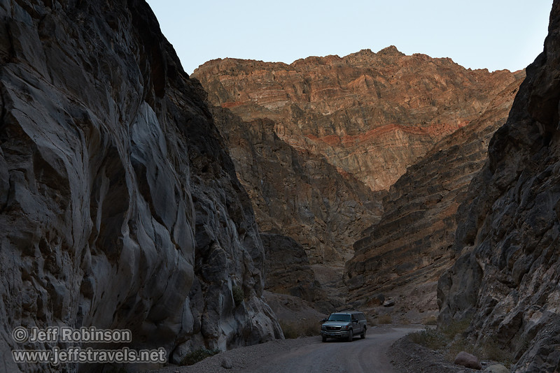 My truck on Titus Canyon Road as it curves through the multiple wall surfaces: smooth rock on the left, angled layers with yellow-brown on the right, and layers with some reds in the background. (3/21/2013, Titus Canyon, Titus Canyon Road, Death Valley NP)<br /> EF24-105mm f/4L IS USM @ 32mm f/9 1/50s ISO800