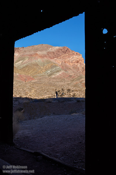 The door of an old building (in the ghost town of Leadfield) frames Lynda taking photos by some bushes in deep shade in the foreground, with a sunlit mountainside beyond with hues of greens, yellows, reds, and browns under blue sky. (3/21/2013, Leadfield (ghost town), Titus Canyon Road, Death Valley NP)<br /> EF24-105mm f/4L IS USM @ 32mm f/11 1/100s ISO100