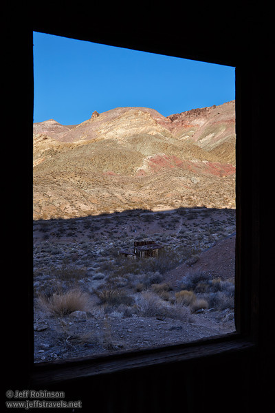 The window of an old building frames a foreground in deep shade, with a sunlit mountainside beyond with hues of greens, yellows, reds, and browns under blue sky. (3/21/2013, Leadfield (ghost town), Titus Canyon Road, Death Valley NP)<br /> EF24-105mm f/4L IS USM @ 28mm f/11 1/100s ISO100