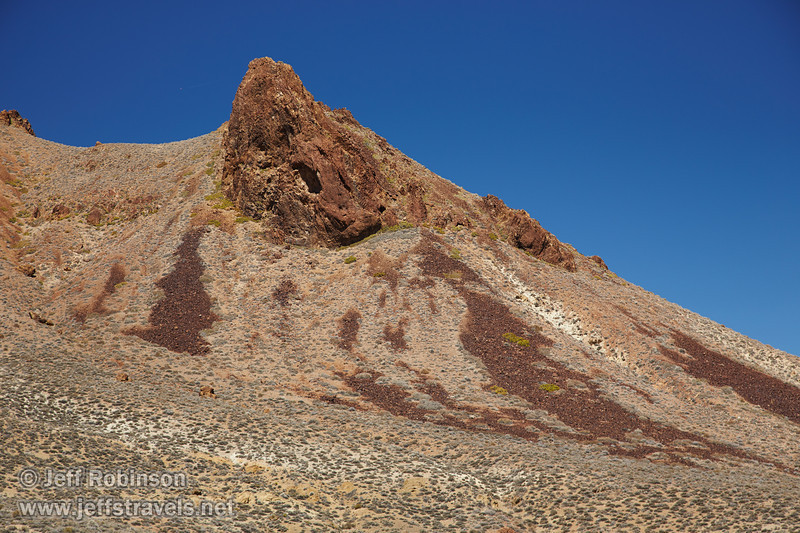 Close up of mountain peaks under deep blue sky. The foreground slopes include pale green brush and yellowish dirt. You can see how reddish-rock has broken off of the mountains to create slides of that color, and deep green bushes surround much of that rockfall.(3/21/2013, Titus Canyon Road, Death Valley NP)<br /> EF24-105mm f/4L IS USM @ 92mm f/7 1/200s ISO200