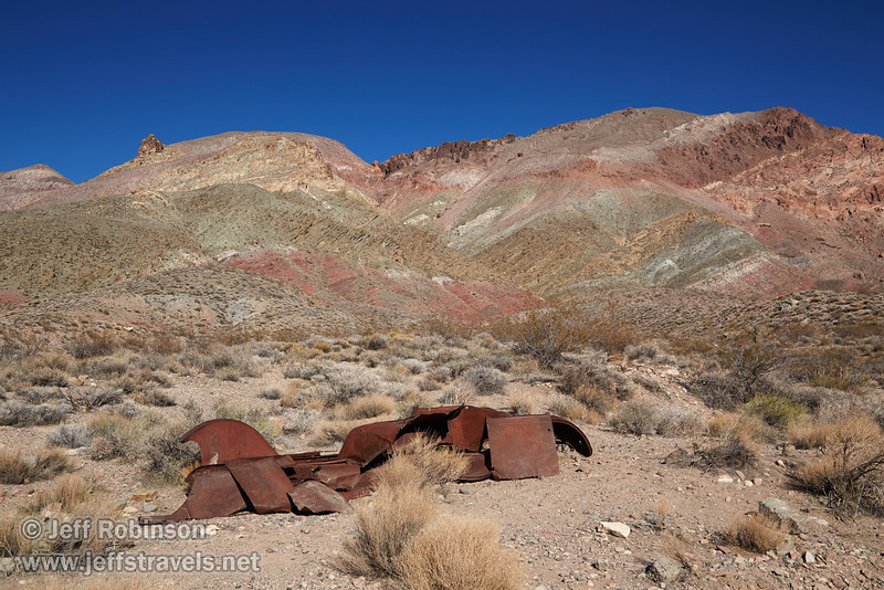 The remains of an old rusted car in the foreground offset the mountain beyond with hues of greens, yellows, reds, and browns under deep blue sky. (3/21/2013, Leadfield (ghost town), Titus Canyon Road, Death Valley NP)<br /> EF24-105mm f/4L IS USM @ 35mm f/11 1/200s ISO400