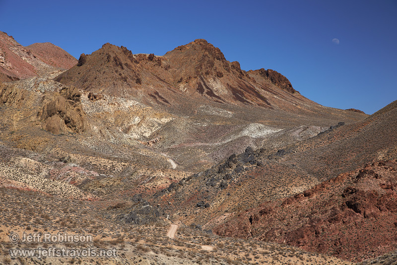 Titus Canyon Rd. looks small compared to the desert mountains with their reds, browns, yellows, and greens under deep blue sky, as the moon rises over the mountains. (3/21/2013, Titus Canyon Road, Death Valley NP)<br /> EF24-105mm f/4L IS USM @ 75mm f/8 1/200s ISO200