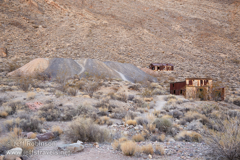 A hillside with light green and yellow desert plants contains the mine tailings from what was probably the main mine shaft of the ghost town of Leadfield, along with two rusted buildings made of corrugated metal that are largely intact. (3/21/2013, Leadfield (ghost town), Titus Canyon Road, Death Valley NP)<br /> EF24-105mm f/4L IS USM @ 40mm f/8 1/125s ISO400